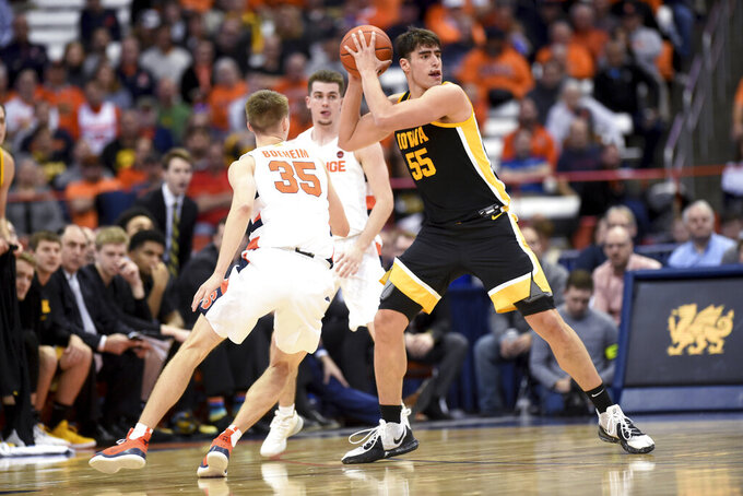Iowa center Luka Garza (55) grabs a rebound from Syracuse guard Buddy Boeheim (35) during an NCAA college basketball game Tuesday, Dec. 3, 2019, in Syracuse, N.Y. (Dennis Nett/The Post-Standard via AP)