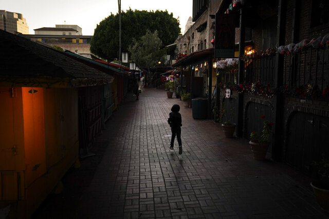 A boy chases a bird on an empty Olvera Street in downtown Los Angeles, Tuesday, Dec. 15, 2020. The tree-covered brick alley typically teeming with tourists is empty. Many of the shops that sell everything from traditional Mexican folk dresses to paintings of artist Frida Kahlo to sombreros are padlocked and the ones open have few, if any, customers. The strains of mariachi trios have fallen silent and the fragrance of taquitos frying has become less pungent. (AP Photo/Jae C. Hong)