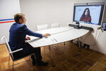 France's President Emmanuel Macron attends a video-conference with New Zealand's Prime Minister Jacinda Ardern at the Fort de Bregancon in Bormes-les-Mimosas, southern France, Friday, May 14, 2021. Tech giants and governments around the world including the U.S., for the first time are gathering virtually Friday to find better ways to stop extremist violence from spreading online, while also respecting freedom of expression. (Clement Mahoudeau/Pool Photo via AP)