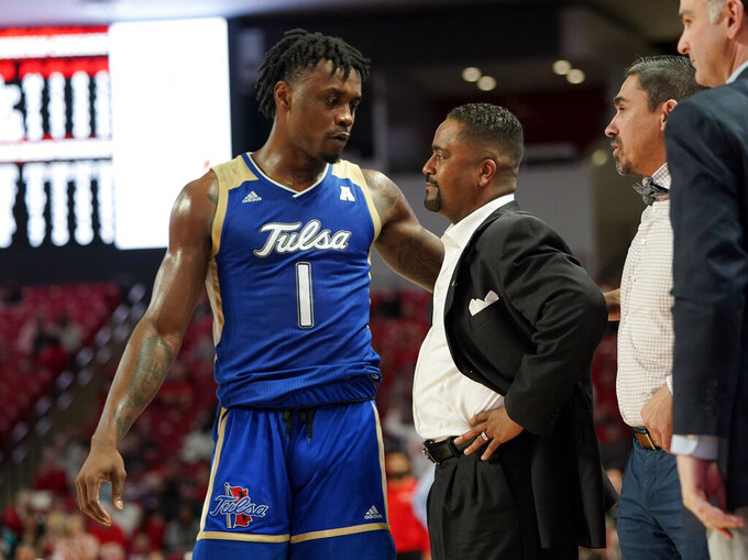 Tulsa's Martins Igbanu (1) talks with coach Frank Haith, center, after Haith was given a second technical foul and ejected from the game during the second half of an NCAA college basketball game against Houston Wednesday, Feb. 19, 2020, in Houston. (AP Photo/David J. Phillip)