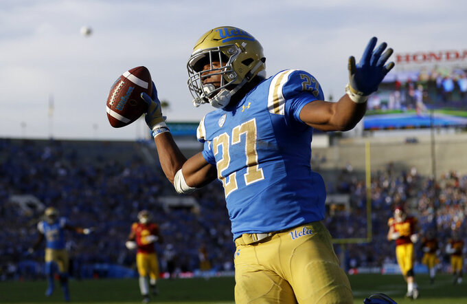UCLA 's Joshua Kelley (27) celebrates after a rushing touchdown against Southern California during the second half of an NCAA college football game Saturday, Nov. 17, 2018, in Pasadena, Calif. (AP Photo/Marcio Jose Sanchez)