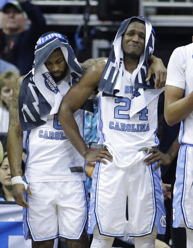 North Carolina's Seventh Woods, left, and Kenny Williams pause near the end of a men's NCAA tournament college basketball Midwest Regional semifinal game against Auburn Friday, March 29, 2019, in Kansas City, Mo. (AP Photo/Charlie Riedel)