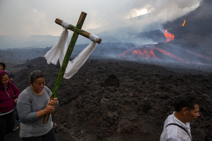 A woman carries a cross during a pilgrimage to pray that the Pacaya volcano decreases its activity in San Vicente Pacaya, Guatemala, Wednesday, May 5, 2021. The volcano, just south of the capital, has been active since early February. (AP Photo/Moises Castillo)