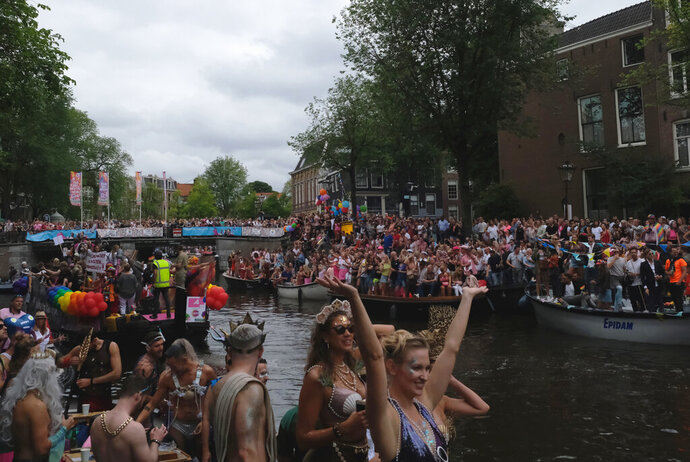 People take part in the Amsterdam Pride Parade, in Amsterdam, Netherlands, Saturday, Aug. 3, 2019. Tens of thousands of spectators are lining one of Amsterdam's main canals to watch a flotilla of decorated boats make their way through the historic waterway as part of the Dutch capital's nine-day pride festival. (AP Photo/Michael Corder)