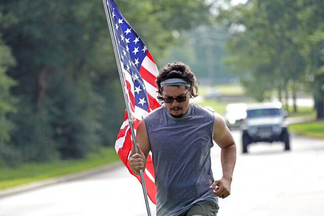 A man, who identifies himself as Dom, jogs along a road with an American flag Saturday, July 4, 2020, in Houston. (AP Photo/David J. Phillip)