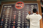 FILE - In this June 3, 2019, file photo, Daniel Espino, a right-handed pitcher from Georgia Premier Academy in Statesboro, Ga., places his name on the draft board after being selected No. 24 by the Cleveland Indians in the first round of the baseball draft in Secaucus, N.J. Baseball's amateur draft this week will look much different because of the coronavirus pandemic, and more permanent changes could be coming soon. (AP Photo/Julio Cortez, File)