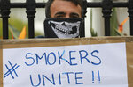 In this June 2, 2020 photo a demonstrator holds a placard during a protest against the tobacco ban outside parliament in Cape Town, South Africa.  An effort to lift South Africa's ban on cigarette sales during the country's coronavirus lockdown has failed. The High Court in the capital, Pretoria, on Friday, June 26, 2020  dismissed a bid by the Fair Trade Independent Tobacco Association, which represents smaller manufacturers. (AP Photo/Nardus Engelbrecht)