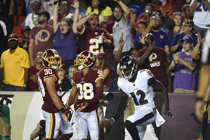 Fans celebrate after Baltimore Ravens wide receiver Jaleel Scott (12) scored a touchdown during the first half of an NFL preseason football game  against the Washington Redskins at FedEx Field in Landover, Md., Thursday, Aug. 29, 2019. Redskins defensive back Troy Apke (30) and teammate defensive back Deion Harris (38) look on. (AP Photo/Susan Walsh)