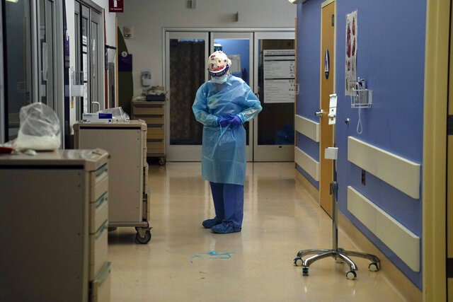 FILE - In this Jan. 7, 2021, file photo, a nurse puts on protective gear in a COVID-19 unit in California. The nation's biggest immunization rollout in history is facing pushback from an unlikely source: health care workers who witnessed COVID-19′s devastation firsthand but are refusing shots in surprising numbers. (AP Photo/Jae C. Hong, File)