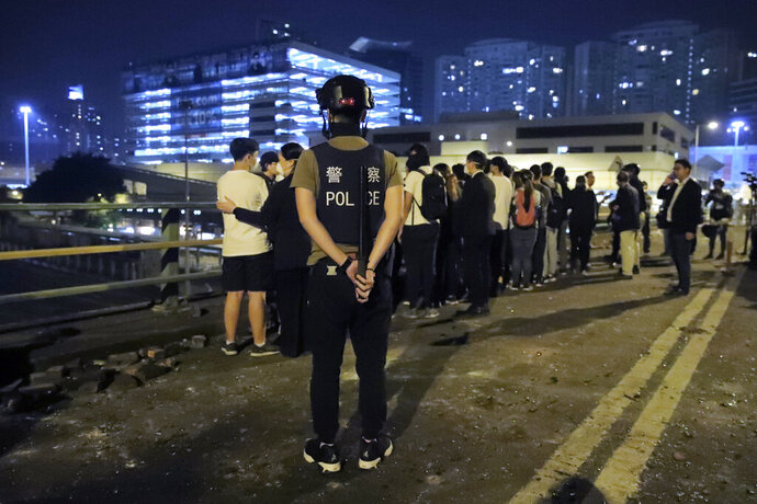 A riot policeman watches over a group of detained people on a bridge in Hong Kong, early Tuesday, Nov. 19, 2019. About 100 anti-government protesters remained holed up at a Hong Kong university Tuesday as a police siege of the campus entered its third day. (AP Photo/Kin Cheung)