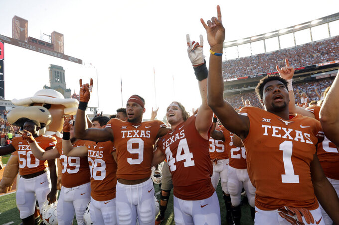 Texas wide receiver Collin Johnson (9) and defensive lineman Breckyn Hager (44) celebrate their win over Baylor with teammates after an NCAA college football game, Saturday, Oct. 13, 2018, in Austin, Texas. (AP Photo/Eric Gay)