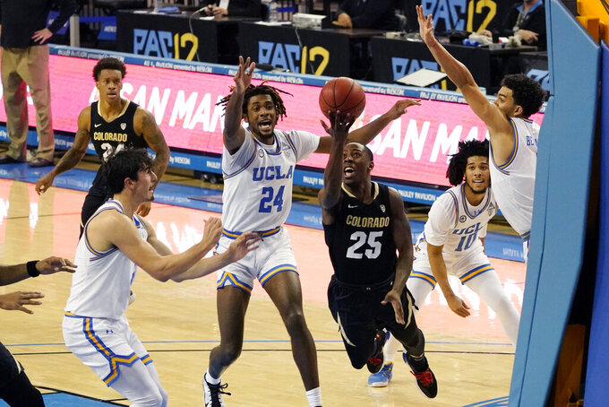 Colorado guard McKinley Wright IV (25) drives to the basket against UCLA during the first half of an NCAA college basketball game Saturday, Jan. 2, 2021, in Los Angeles. (AP Photo/Marcio Jose Sanchez)