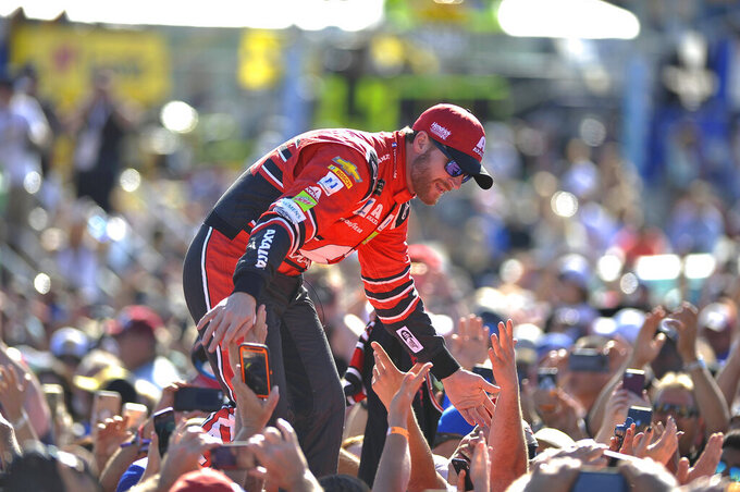 FILE - In this Nov. 19, 2017, file photo, Dale Earnhardt Jr. interacts with fans during driver introductions before a NASCAR Cup Series auto race at Homestead-Miami Speedway in Homestead, Fla. Dale Earnhardt Jr. is returning to the track Saturday, June 13, 2020, getting behind the wheel for an Xfinity race at Homestead-Miami Speedway -- the place where his Cup Series career ended three years ago. (AP Photo/Terry Renna, File)