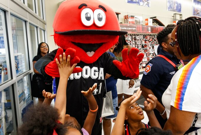 In this July 18, 2019 photo, children from the YMCA Westside and Salvation Army high-five Looie the Lookout before a shopping spree at Academy Sports and Outdoors in Chattanooga, Tenn.  The Chattanooga Lookouts announced Wednesday, March 31, 2021 on Twitter that the costume for Looie the Lookout has been returned home safe.  The team told authorities that the mascot's costume was stolen from an office at AT&T Field on Tuesday, along with hundreds of dollars in merchandise and equipment were also stolen.  (Doug Strickland/Chattanooga Times Free Press via AP)