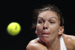 In this Friday, Nov. 1, 2019, file photo, Simona Halep of Romania eyes on the ball as she plays against Karolina Pliskova of the Czech Republic during the WTA Finals Tennis Tournament at the Shenzhen Bay Sports Center in Shenzhen, China's Guangdong province. (AP Photo/Andy Wong, File)