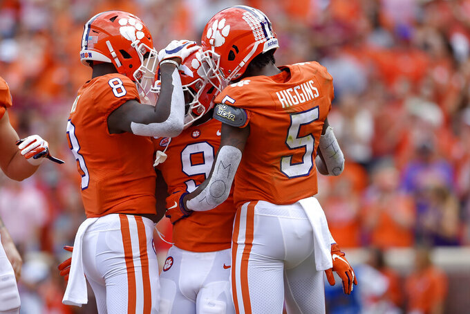 Clemson's Travis Etienne, center, celebrates a touchdown with teammates Tee Higgins, right, and Justyn Ross during the first half of an NCAA college football game against Florida State Saturday, Oct. 12, 2019, in Clemson, S.C. (AP Photo/Richard Shiro)