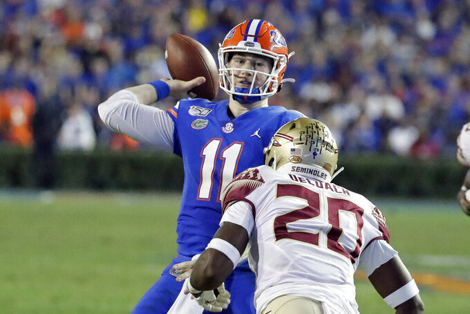 Florida quarterback Kyle Trask (11) throws a pass over Florida State linebacker Kalen DeLoach (20) during the first half of an NCAA college football game Saturday, Nov. 30, 2019, in Gainesville, Fla. (AP Photo/John Raoux)
