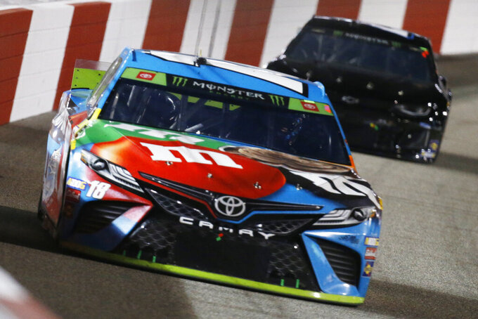 Kyle Busch (18) drives into turn one during the NASCAR Monster Energy Cup series auto race at Richmond Raceway in Richmond, Va., Saturday, Sept. 21, 2019. (AP Photo/Steve Helber)