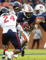 Auburn running back Kam Martin (9) hits a hole as Liberty defensive back Malik Matthews (24) closes in during the first half of an NCAA college football game, Saturday, Nov. 17, 2018, in Auburn, Ala. (AP Photo/Vasha Hunt)