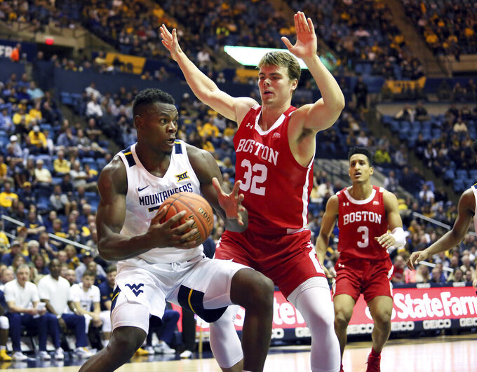 West Virginia forward Oscar Tshiebwe (34) is defended by Boston University forward Jack Hemphill (32) while guard Alex Vilarino (3) watches during the second half of an NCAA college basketball game Friday, Nov. 22, 2019, in Morgantown, W.Va. (AP Photo/Kathleen Batten)