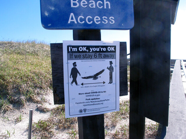 A sign is posted at the entrance to Island Beach State Park in New Jersey, Saturday, May 2, 2020, warning beachgoers to separate themselves by at least six feet on the day New Jersey's state parks reopened after a closure brought on by the coronavirus outbreak. (AP Photo/Wayne Parry)