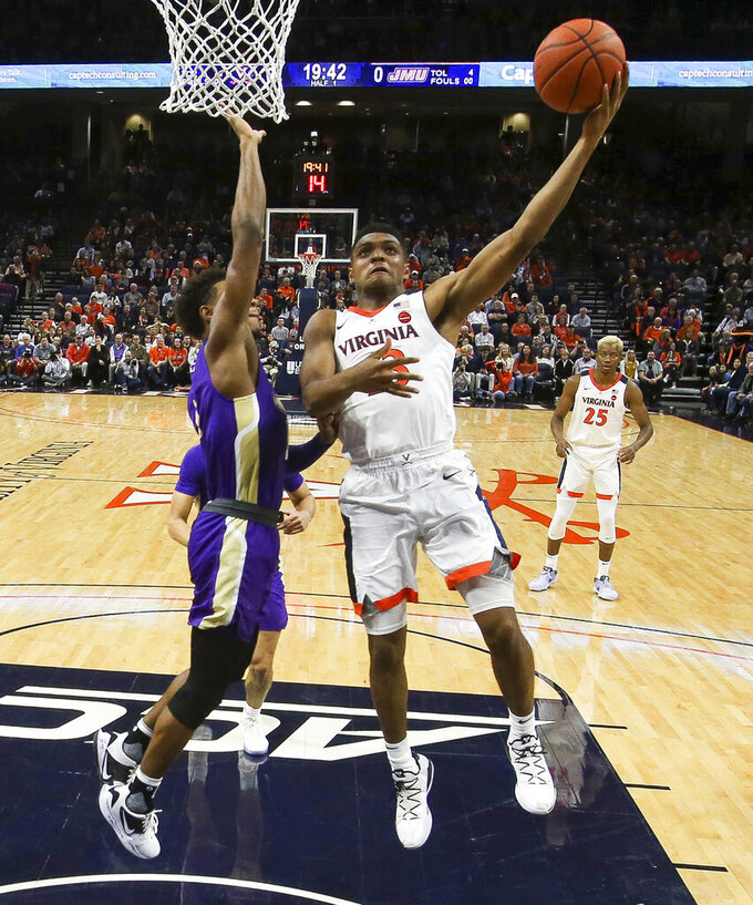 Virginia guard Casey Morsell (13) shoots next to James Madison guard Matt Lewis, left, during an NCAA college basketball game in Charlottesville, Va., Sunday, Nov. 10, 2019. (AP Photo/Andrew Shurtleff)
