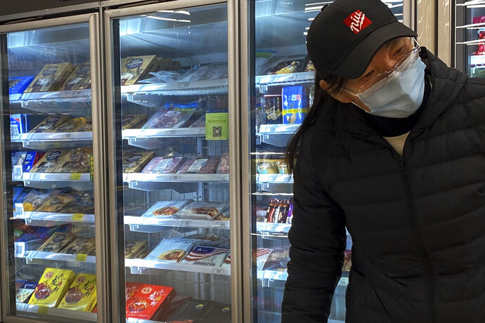 A woman wearing a face mask to help curb the spread of the coronavirus walks by a fridge displaying frozen meats at a supermarket in Beijing, Tuesday, Nov. 24, 2020. China has stirred controversy with claims it has detected the coronavirus on packages of imported frozen food. (AP Photo/Andy Wong)