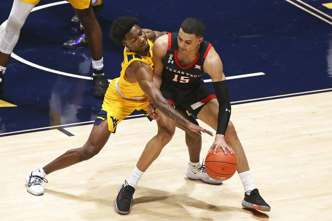 Texas Tech guard Kevin McCullar (15) is defended by West Virginia guard Kedrian Johnson (0) during the first half of an NCAA college basketball game Monday, Jan. 25, 2021, in Morgantown, W.Va. (AP Photo/Kathleen Batten)