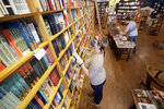 In this Thursday, June 25, 2020, photo, Jordan Vroon, left, takes inventory in Parnassus Books in Nashville, Tenn. The independent bookstore, owned by novelist Ann Patchett and Karen Hayes, opened and thrived while others were closing their doors and is once again defying the odds during the coronavirus pandemic. (AP Photo/Mark Humphrey)