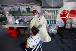 Nurse Tanya Markos administers a test for coronavirus at a mobile COVID-19 testing unit, Thursday, July 2, 2020, in Lawrence, Mass. (AP Photo/Elise Amendola)