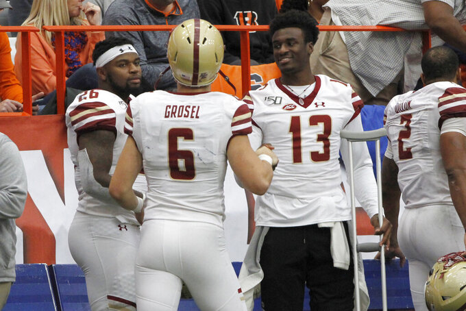 Boston College's Dennis Grosel, center, celebrates with teammates Anthony Brown, right, and David Bailey, left, late in the fourth quarter of an NCAA college football game against Syracuse in Syracuse, N.Y., Saturday, Nov. 2, 2019. Boston College won 58-27. (AP Photo/Nick Lisi)