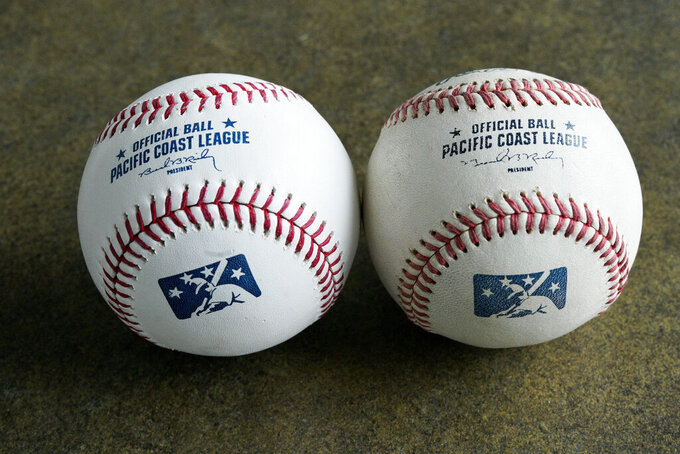 FILE - In this May 7, 2019, file photo, a new official Pacific Coast League baseball, left, is seen beside a baseball from the previous year in Papillion, Neb. Major League Baseball has reorganized its minor leagues in a 120-team regional alignment, MLB announced, Friday, Feb. 12, 2021.  The leagues have not yet been named and Major league owners, Commissioner Rob Manfred and his staff have not decided whether to retain the traditional names of the leagues, such as Pacific Coast League. (AP Photo/Nati Harnik, File)