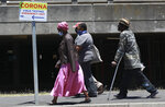People pass a sign at Groote Schuur Hospital in Cape Town, South Africa, indicating a COVID testing station Tuesday, Dec. 29, 2020. South African President Cyril Ramaphosa has declared the wearing of masks compulsory and has reimposed a ban on the sales of alcohol and ordered the closure of all bars and beaches as part of new restrictions to help the country battle a resurgence of the coronavirus, including a new variant. (AP Photo/Nardus Engelbrecht)