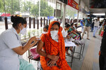 A health worker administers the vaccine for COVID-19 during a special vaccination drive by the municipal corporation at a bus stand in Ahmedabad, India, Friday, Sept. 17, 2021. (AP Photo/Ajit Solanki)