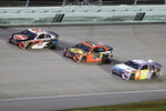 Christopher Bell (95), Martin Truex Jr. (19) and Kyle Busch (18) come through a turn during a NASCAR Cup Series auto race Sunday, June 14, 2020, in Homestead, Fla. (AP Photo/Wilfredo Lee)