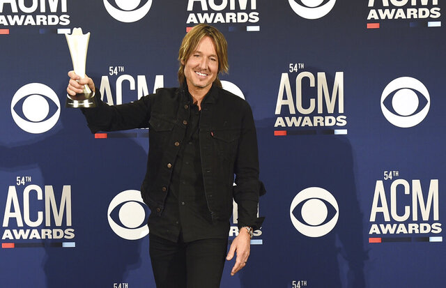 FILE - In this April 7, 2019, file photo, Keith Urban poses in the press room with the award for entertainer of the year at the 54th annual Academy of Country Music Awards in Las Vegas. The Academy of Country Music had to postpone its upcoming awards show, to be hosted by Urban, because of the spreading coronavirus, but CBS will air a new television special featuring country stars performing from their homes. (Photo by Jordan Strauss/Invision/AP, File)