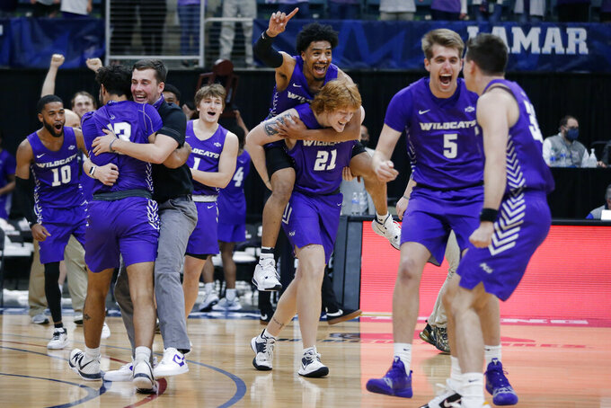 Abilene Christian players celebrate a 79-45 win against Nicholls State at the end of an NCAA college basketball game for the Southland Conference men's tournament championship Saturday, March 13, 2021, in Katy, Texas. (AP Photo/Michael Wyke)