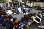 Muslim youth cordon a place as others pray during a protest rally against a new citizenship law, in Kolkata, India, Tuesday, Jan. 21, 2020. India has been embroiled in protests since December, when Parliament passed a bill amending the country's citizenship law. The new law provides a fast track to naturalization for some migrants who entered the country illegally while fleeing religious persecution. But it excludes Muslims, which critics say is discriminatory and a violation of India's Constitution. (AP Photo/Bikas Das)