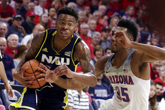 FILE - In this Nov. 10, 2017, file photo, Northern Arizona guard Karl Harris drives on Arizona guard Allonzo Trier (35) during the first half during an NCAA college basketball game in Tucson, Ariz. Another dream, of playing in the NCAA Tournament, became a reality when Northern Kentucky clinched the Horizon League tournament title in March.  Mere hours later, it was snatched away by a pandemic spiderwebbing across the globe.  (AP Photo/Rick Scuteri, FIle)