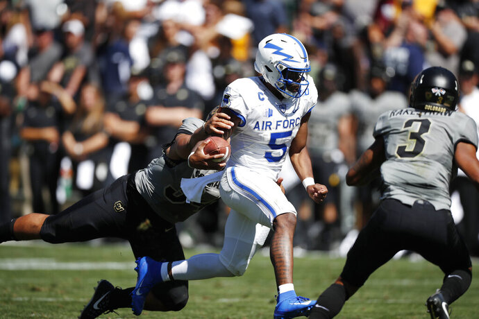 Air Force quarterback Donald Hammond III, center, drives for a short gain as Colorado safety Sam Noyer, left, and safety Derrion Rakestraw cover in the second half of an NCAA college football game Saturday, Sept. 14, 2019, in Boulder, Colo. Air Force won 30-23 in overtime. (AP Photo/David Zalubowski)