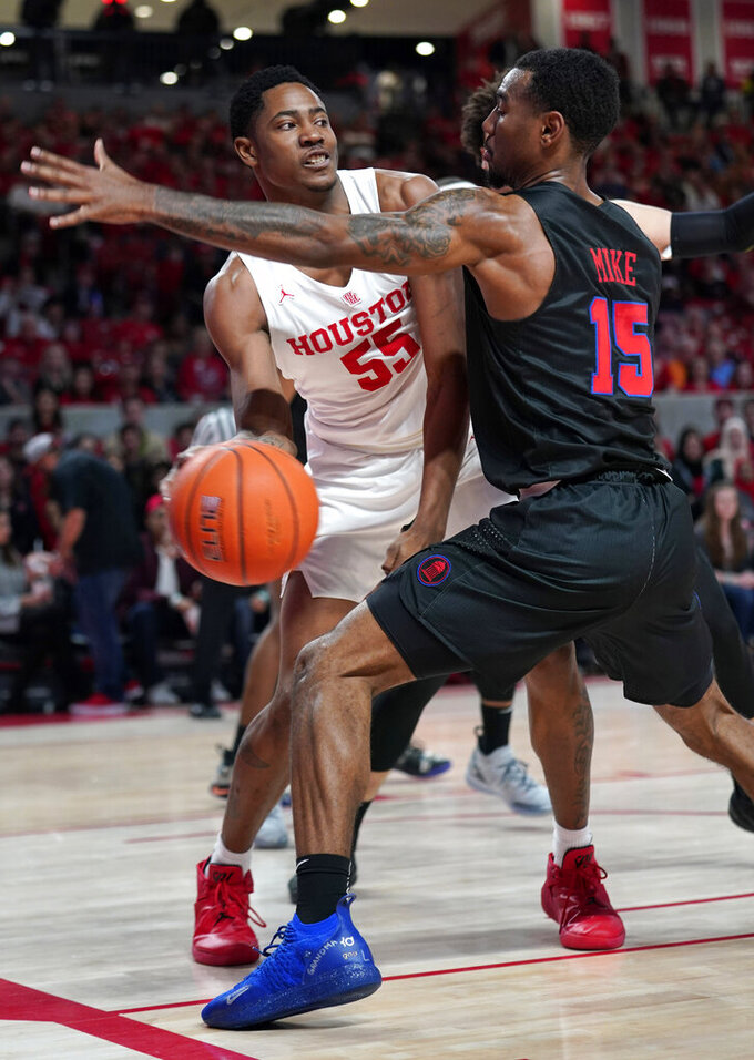 Houston's Brison Gresham (55) passes the ball around Southern Methodist's Isiaha Mike (15) during the first half of an NCAA college basketball game Thursday, March 7, 2019, in Houston. (AP Photo/David J. Phillip)