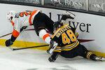 Philadelphia Flyers left wing Scott Laughton (21) and Boston Bruins defenseman Matt Grzelcyk (48) grapple for the puck along the boards during the second period of an NHL hockey game Thursday, Jan. 21, 2021, in Boston. (AP Photo/Elise Amendola)