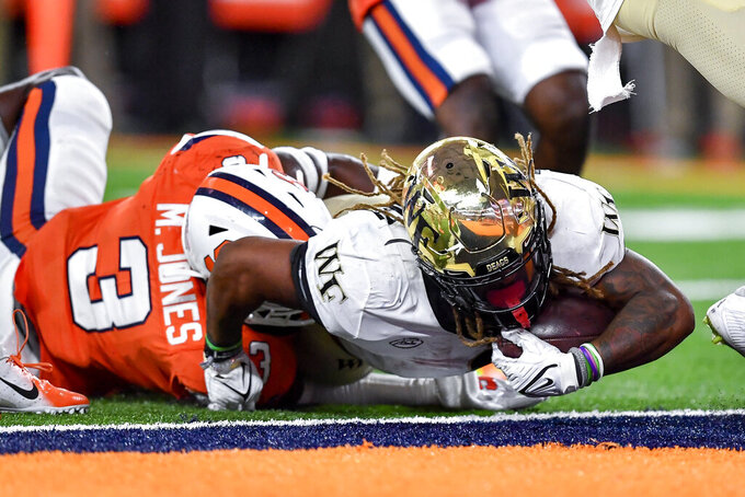 Wake Forest running back Christian Beal-Smith (1) dives to the end zone for a touchdown in front of Syracuse linebacker Mikel Jones (3) during the second half of an NCAA college football game in Syracuse, N.Y., Saturday, Oct. 9, 2021. (AP Photo/Adrian Kraus)