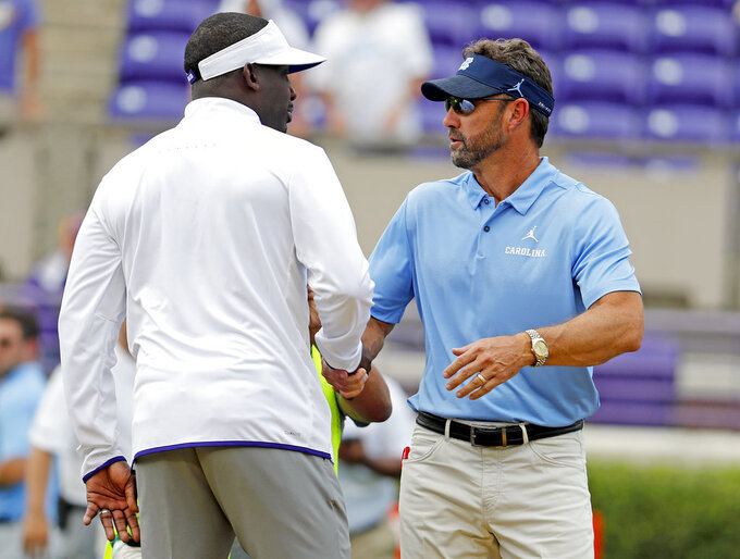 East Carolina head coach Scottie Montgomery, left, speaks with North Carolina head coach Larry Fedora, right, prior to their game in Greenville, N.C., Saturday, Sept. 8, 2018. (AP Photo/Karl B DeBlaker)