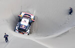 Driver Sebastien Loeb, of France,left, and co-driver Daniel Elena, of Monaco, look at their stuck Peugeot during the 5th of the 2018 Dakar Rally between San Juan de Marcona and Arequipa, Peru, Wednesday, Jan. 10, 2018. They withdrew from the race after Elena sustained an injury when they got stuck. (Franck Fife /Pool Photo via AP)