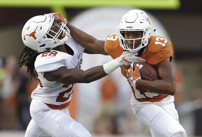 "FILE - In this Saturday, April 21, 2018 file photo, Texas wide receiver Jerrod Heard (13) is hit by defensive back Jarmarquis Durst (28) after making a catch during the NCAA college football team's Orange-White spring game in Austin, Texas. Once upon a time, Jerrod Heard had ""the juice."" He was the quarterback of the future for the Texas Longhorns and he'd just smashed Vince Young's single-game school for total offense. He could throw. He could run. He could do just about everything. Then all that juice dried up with a whole lot of losing. A fifth-year senior, Heard heads into his final home game this week as a fifth-option wide receiver and special teams guy. (AP Photo/Eric Gay, File)"