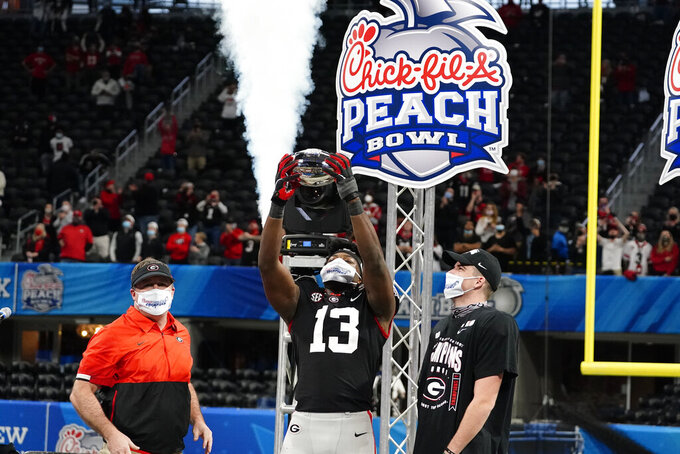 Georgia head coach Kirby Smart, watches Georgia linebacker Azeez Ojulari hold the championship tropy as Georgia place kicker Jack Podlesny (96) looks on after the Peach Bowl NCAA college football gameagainst Cincinnati, Friday, Jan. 1, 2021, in Atlanta. Georgia won 22-21. (AP Photo/Brynn Anderson)