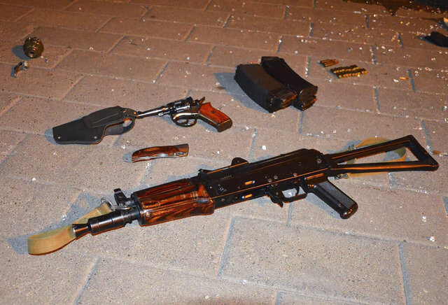 Weapon that belonged to an assailant, who seized a long-distance bus with 13 hostages, on the ground after police officers captured the assailant in the city centre of Lutsk, some 400 kilometers (250 miles) west of Kyiv, Ukraine late Tuesday July 21, 2020. Ukrainian police say the armed man who seized hostages aboard a long-distance bus in the western city of Lutsk has been detained and all the people he held have been freed unharmed after a standoff that lasted more than 12 hours. (Ukrainian Police Press Office via AP)