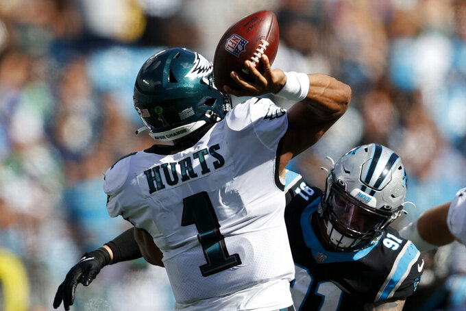El quarterback Jalen Hurts (1) lanza un pase por los Eagles de Filadelfia bajo la presión del defensive end Morgan Fox, de los Panthers de Carolina, en partido de NFL el domingo 10 de octubre de 2021, en Charlotte, Carolina del Norte. (AP Foto/Nell Redmond)
