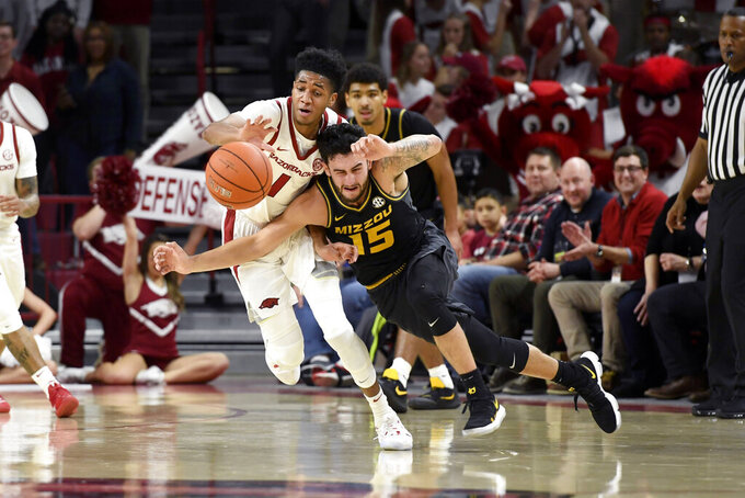 Arkansas guard Isaiah Joe (1) steals the ball from Missouri guard Jordan Geist (15) during the first half of an NCAA college basketball game, Wednesday, Jan. 23, 2019, in Fayetteville, Ark. (AP Photo/Michael Woods)